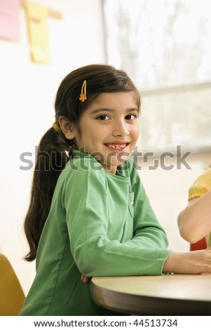 Young girl student sitting in school classroom. Vertically framed shot.