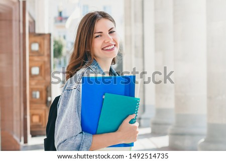 Young girl student smiling on a university background. Happy girl student passed the session