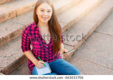 Young girl student with phone and notepad #663615706