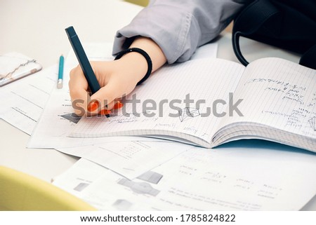 Young girl studying using pen and a notebook, preparation for SAT, preparation for ACT, CLT,  preparation for math exam, standardized test preparation Stok fotoğraf ©