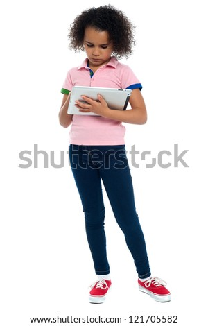 Young girl super busy in operating new tablet device. Dressed in casuals.