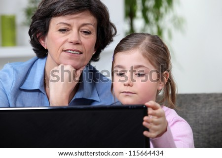 Young girl surfing the Internet with her grandmother
