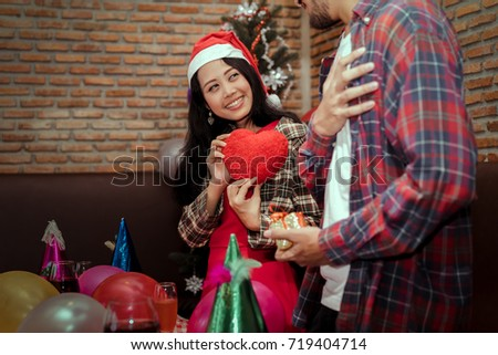 Young girl surprise gift heart to boyfriend couple together in christmas party with santa hat celebrate lover at home copy space the left #719404714