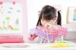young girl sweing pad craft using plastic needle and yarn for homeschooling