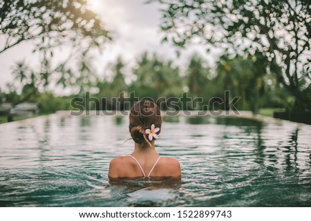 Young girl swimming in infinity pool with in private villa resort. Travelling to Ubud, Bali.