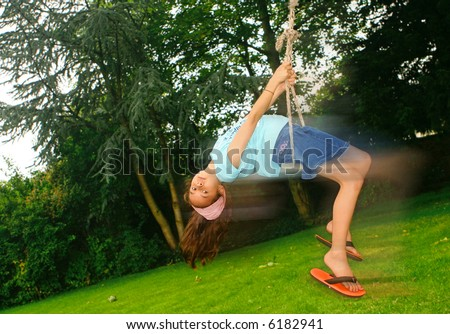 Young girl swinging back on a rope swing attached to a tree.