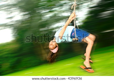 Young girl swinging fast while lying down backwards on a rope swing attached to a tree.
