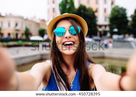 Shutterstock Young girl take selfie from hands with phone on summer city street. Urban life concept.