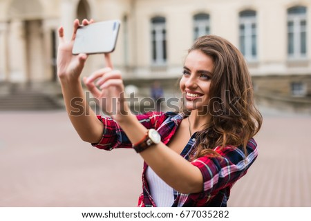 Young girl take selfie from hands with phone on summer city street urban life concept