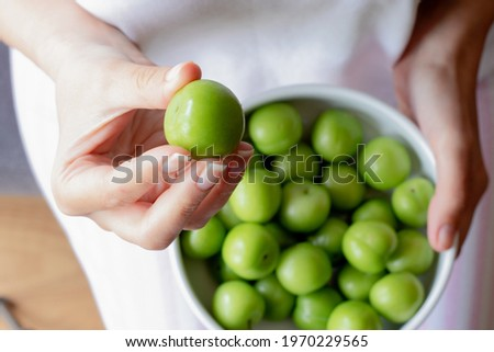 young girl takes one plum from a plate of plums in her arms to eat. The young girl's hand is holding a sour green plum. Healthy nutrition
