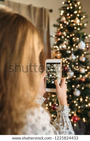 Young girl  taking  a picture of  a Christmas tree with her smartphone.