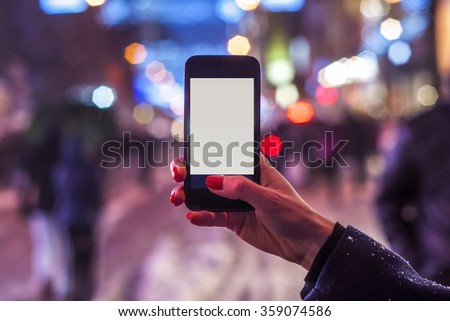 Young girl taking night view photos using mobile phone on the street