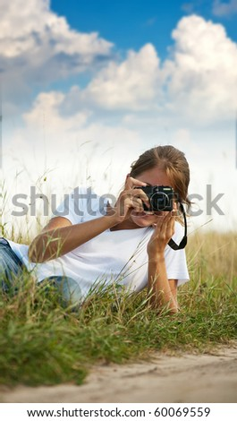 Young girl taking photo with camera against blue sky