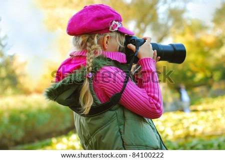 young girl taking photos by professional digital camera in autumn park