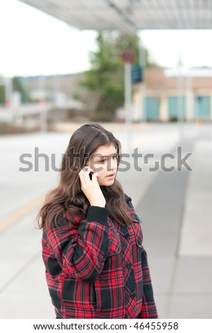 Young girl talking on her cell phone at bus stop. Shallow depth of field.