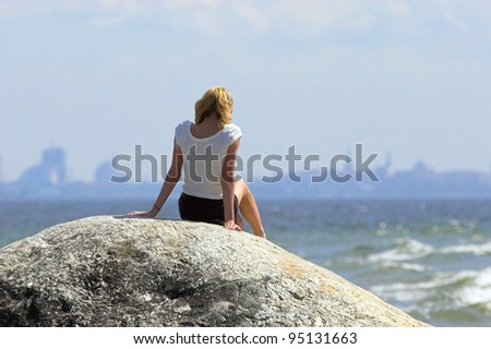 young girl tanning on a huge stone in Naissaar Island and looking  at the silhouette of Tallinn