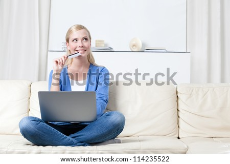 Young girl thinks about purchasing through the internet sitting on the sofa - stock photo