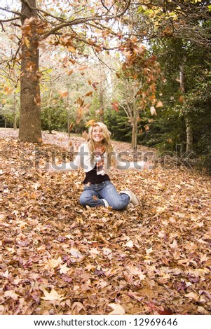 young girl throwing Autumn leaves in the air
