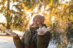 Young girl throws snow up with a nice smile/Happy young girl plays with a snow in sunny winter day/ throw snow on the sun
