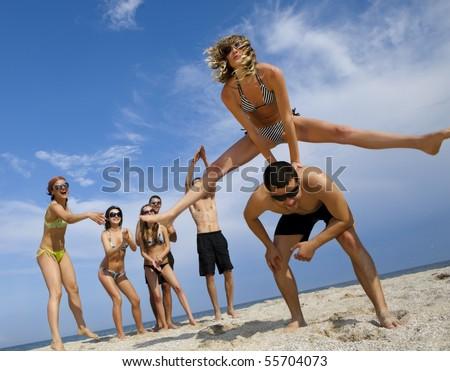 Young girl to jump across her boyfriend against joyful team of friends having fun at the beach #55704073
