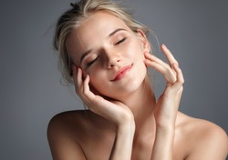 Young girl touching her face. Photo of blonde girl with perfect skin on grey background. Youth and Beauty