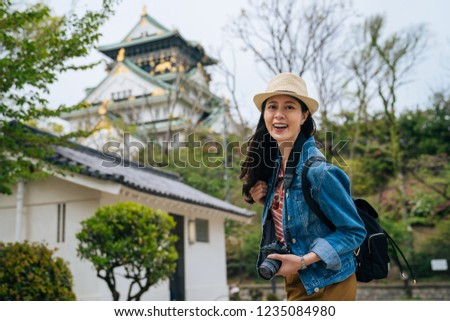 young girl tourist face camera smiling holding slr camera. professional photographer always travel with her digicam. lady traveler visit himeji castle from osaka on sunny day with green trees around.