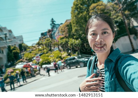 young girl tourist face camera smiling taking selfie while sightseeing in lombard street in San Francisco United State. woman traveler make self photo on sunny day in famous attraction outdoors. #1482913151