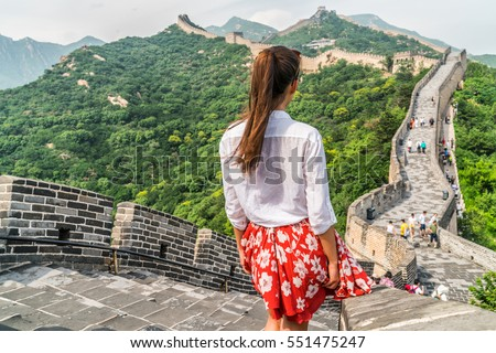 Young girl tourist from behind looking at view of Great Wall of China at famous Badaling tourism attraction during travel vacation in Beijing. Asia summer holidays. #551475247