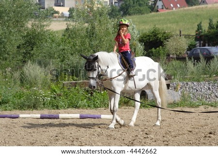 Young girl training on white horse