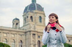 Young girl traveler with white jacket straighten red scarf and looking away, Kunsthistorisches Museum of Art History or Fine Arts in Vienna city historical centre background, vacation in Austria