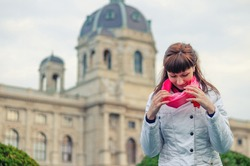 Young girl traveler with white jacket straighten red scarf and looking down, Kunsthistorisches Museum of Art History or Fine Arts in Vienna city historical centre background, vacation in Austria