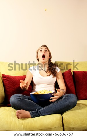 Young girl trying to catch a popcorn piece with her mouth after throwing in the air