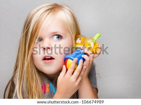 Young girl trying to use a toy hammer as a phone or just having fun playing make believe