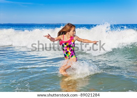 Young girl turning to run from an incoming wave - stock photo