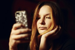 Young girl using a handheld mobile phone texting a message