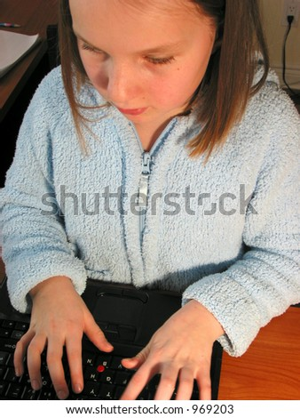 Young girl using a laptop computer, focus on hands