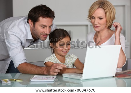Young girl using a laptop computer with her parents