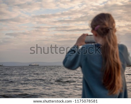 Young girl using her phone to take picture of cruise liner in the ocean. Girl is out of focus, cruise ship is in focus,