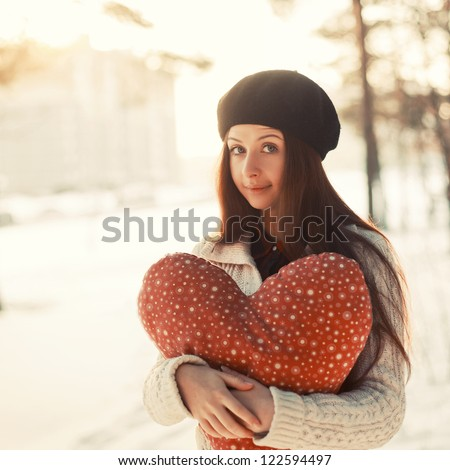 Young girl valentine day portrait. Holding big heart in hands