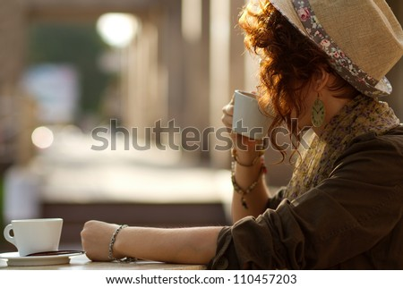 Young girl waiting for somebody in a cafe at sunset
