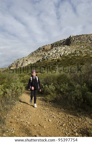 Young girl walking along mountain path - stock photo