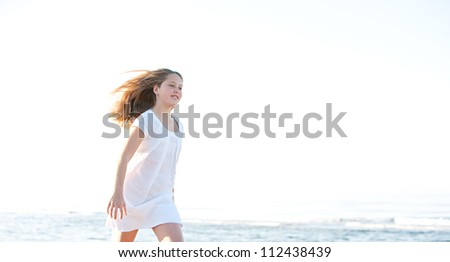 Young girl walking along the shore on a sunny beach with the horizon in the background, smiling and with her hair floating in the breeze.