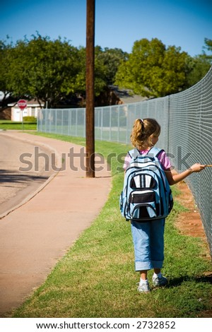 Young girl walking by school yard on first day of school with backpack and pencil