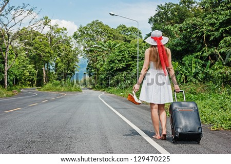 young girl walking down the road with a suitcase