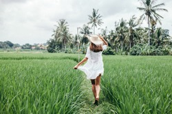 Young girl walking in rice field in Ubud, Bali. Trevelling to clean places of Earth and discovering beauty of nature.