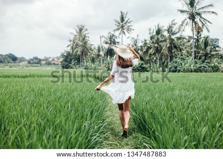 Young girl walking in rice field in Ubud, Bali. Trevelling to clean places of Earth and discovering beauty of nature. #1347487883