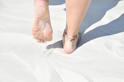 Young girl walking on the beach barefoot. Tiny woman feet on the white sand with the anklet of multicoloured threads.