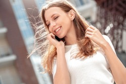 Young girl walking on the city street looking aside laughing happu face close-up blurred background