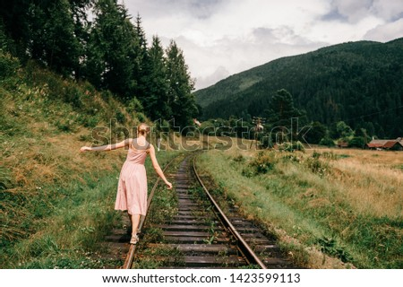 Young girl walking on the railway. Woman in pink dress walking on railroad tracks