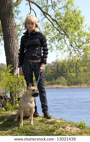 Young girl Walking with dog in the spring forest near river